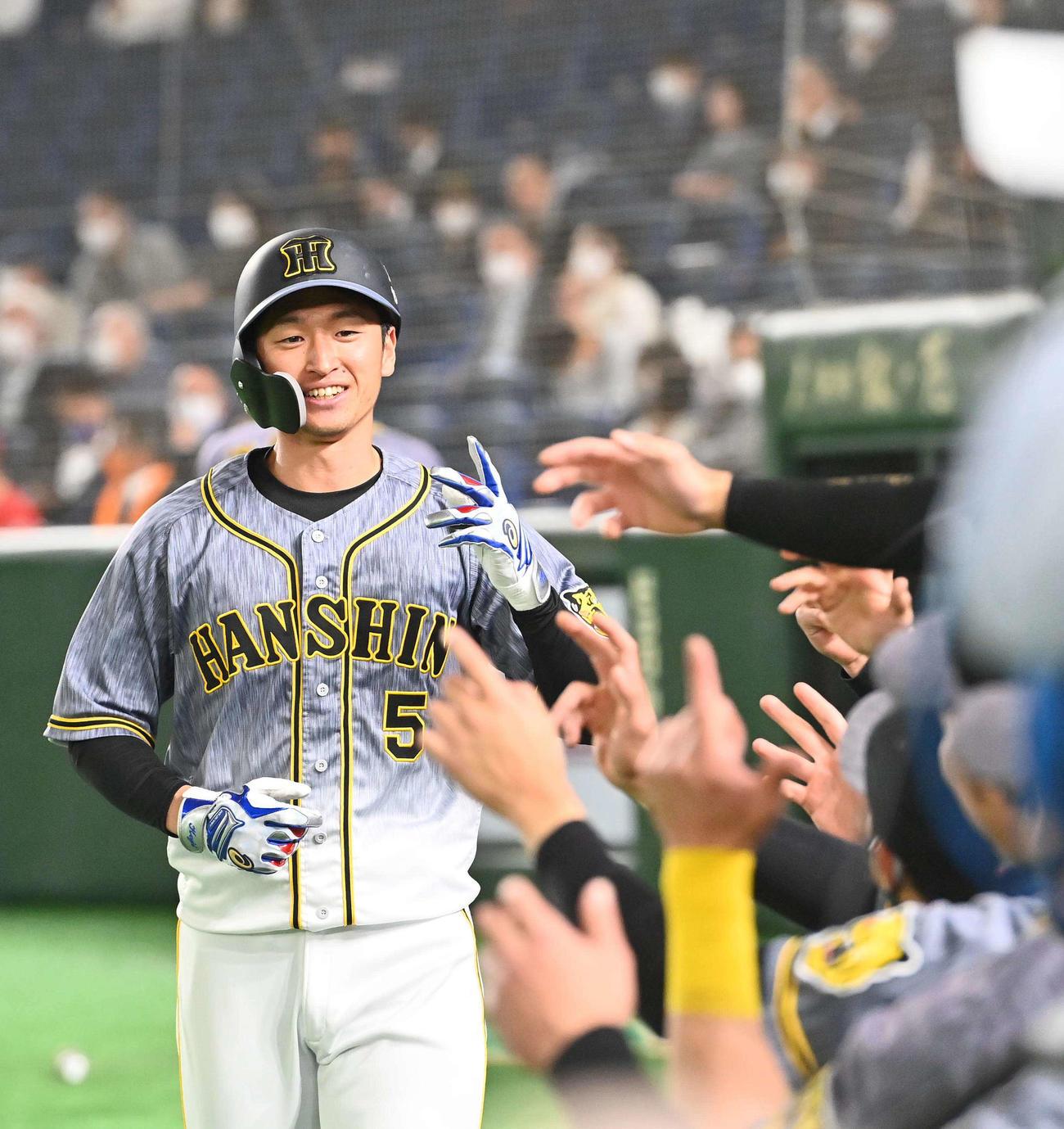 巨人対阪神 1回表阪神無死、右越えに先頭打者本塁打を放ちナインの出迎えに笑顔を見せる近本(撮影・上田博志)