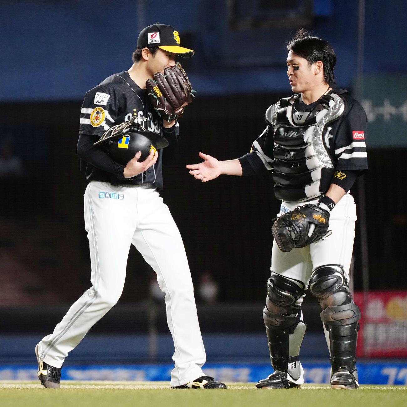 ロッテ対ソフトバンク 8回裏終了後、ソフトバンク捕手甲斐(右)にヘルメットを渡す4番手の高橋純(撮影・江口和貴)