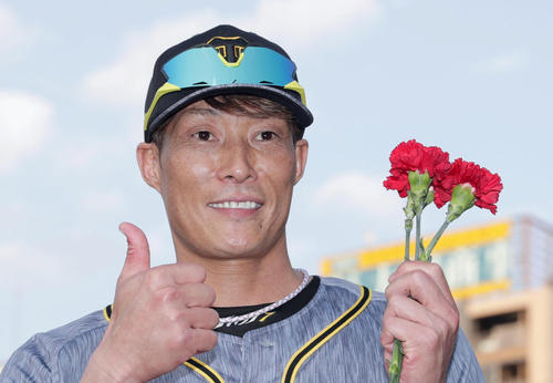 カーネーションを手に笑顔でサムアップポーズを決める阪神糸井(撮影・前田充)
