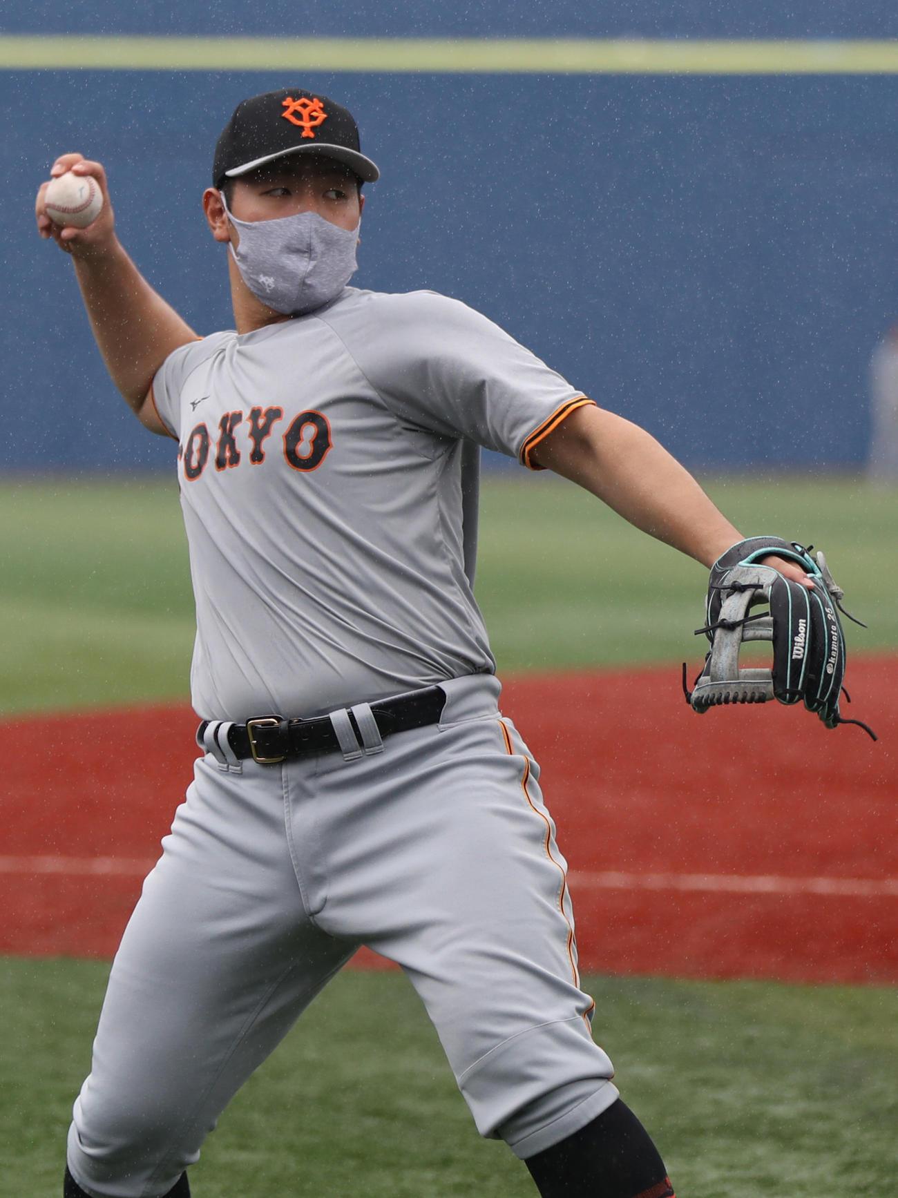 DeNA対巨人 雨の横浜スタジアムでキャッチボールをする岡本和(撮影・狩俣裕三)