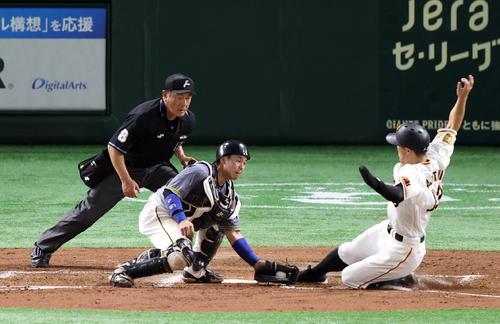 巨人対阪神 3回裏巨人1死満塁、岡本和の犠飛で生還する梶谷(右)。左は梅野(撮影・狩俣裕三)