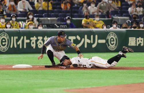 巨人対阪神 2回裏巨人1死一塁、吉川尚の中前打で三塁を狙うもタッチアウトとなる一塁走者若林(右)。三塁手佐藤輝(撮影・足立雅史)