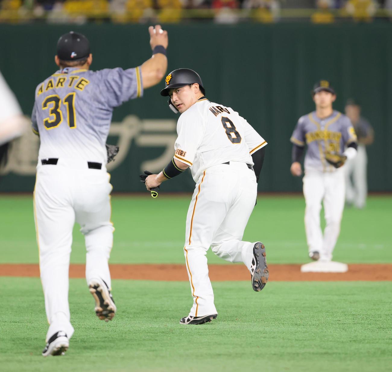 巨人対阪神 1回裏巨人2死一、三塁、一塁走者丸(中央)が一二塁間で挟まれる間に三塁走者梶谷が生還に成功する(撮影・足立雅史)