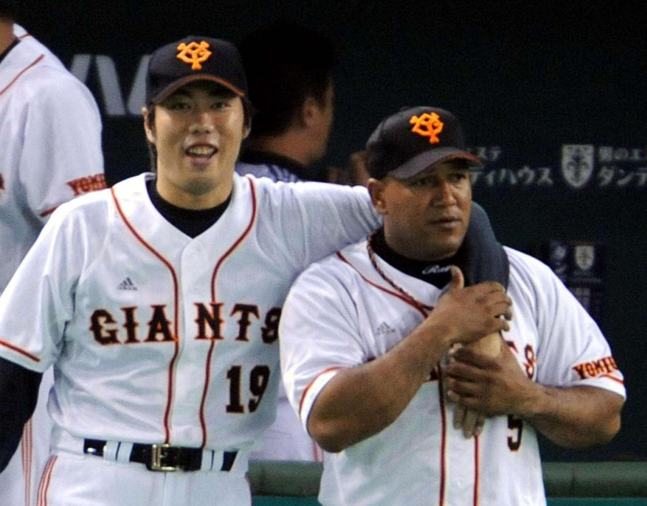 アレックス・ラミレス(右)と肩を組んで、笑顔を見せる上原浩治(2008年10月23日)