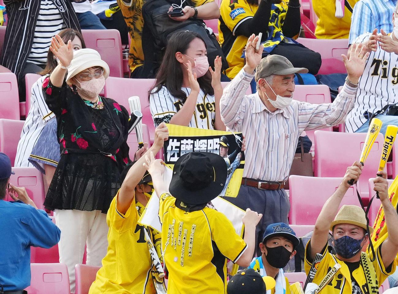 楽天対阪神 試合後、ヒーローインタビューを受ける阪神佐藤輝に手を振る祖父勲さん(中央右)と祖母美智恵さん(同左)(撮影・江口和貴)