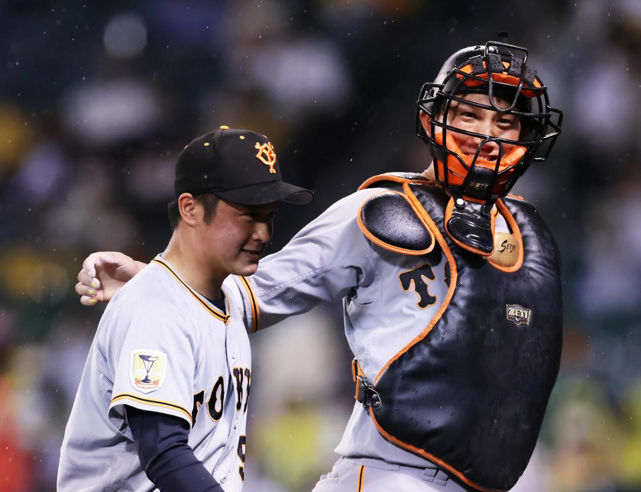 阪神対巨人 8回から登板した巨人戸田(左)の肩を笑顔でたたく小林(撮影・足立雅史)