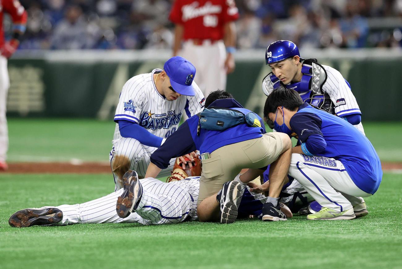 DeNA対広島 3回表広島無死一、三塁、林に第1球を投げた時、突然倒れるDeNAピープルズ。心配し集まるソト(左)と伊藤光(撮影・鈴木正人)