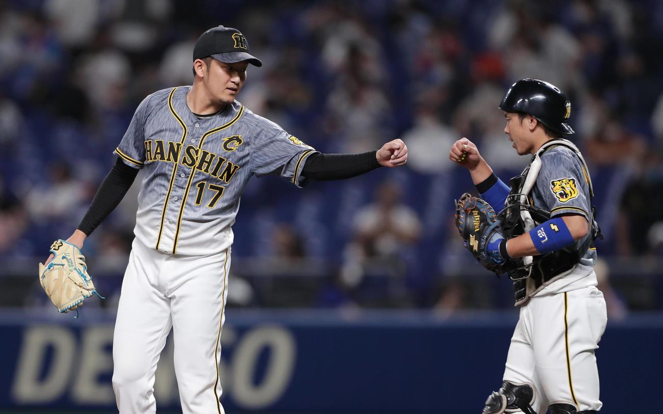 中日対阪神 中日に勝利しグータッチを交わす阪神岩貞(左)と梅野(撮影・前田充)