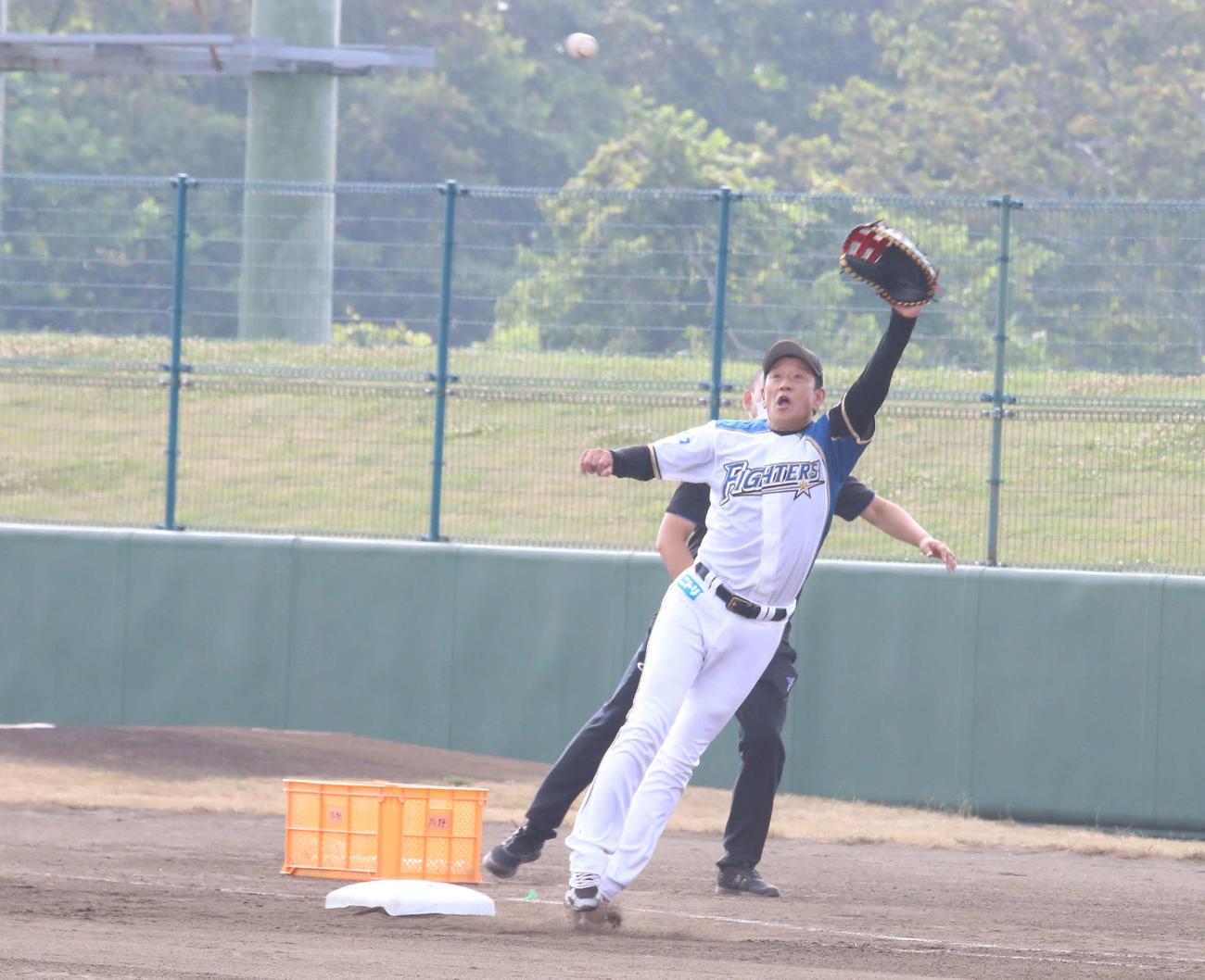 地元中学生の送球を伸び上がって捕ろうとする日本ハム栗山監督(撮影・中島宙恵)