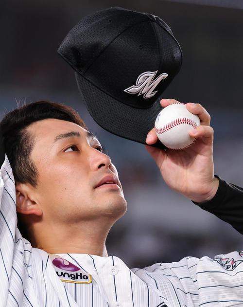 ロッテ対楽天 投球練習中も帽子の文字を見つめ集中力するロッテ先発の小島(撮影・垰建太)