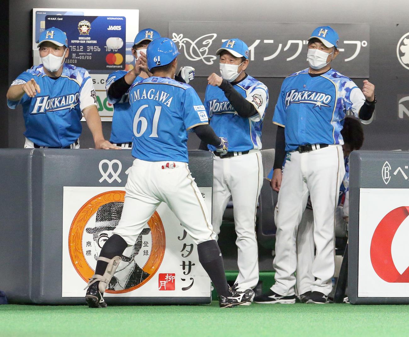 日本ハム対ソフトバンク 2回日本ハム1死二塁、プロ初安打で初本塁打を放った今川を出迎える栗山監督(右から2人目)(撮影・佐藤翔太)