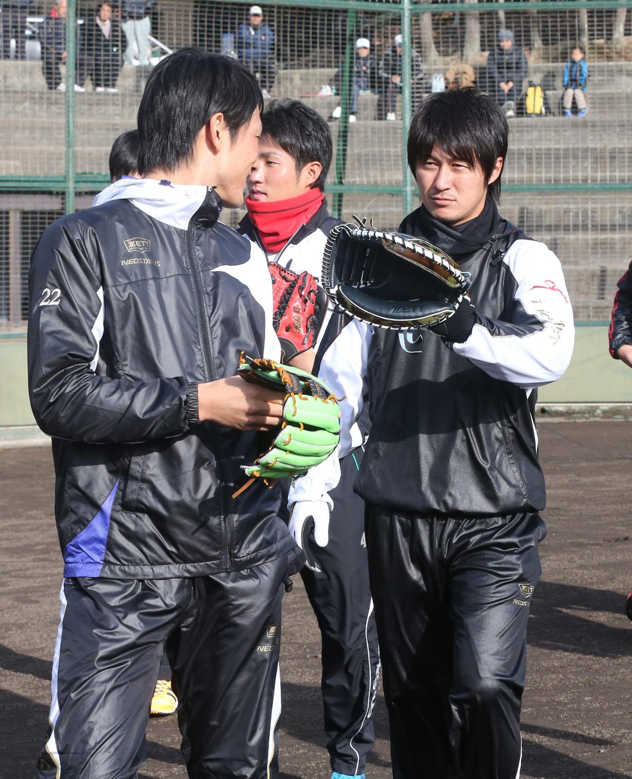 キャッチャーミットを手に巨人小林(左)に話し掛ける俊介(12月26日)