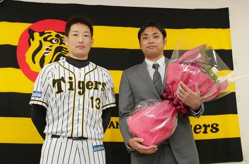 引退会見にサプライズで登場した阪神岩崎(左)から花束を受け取った桑原(撮影・前田充)