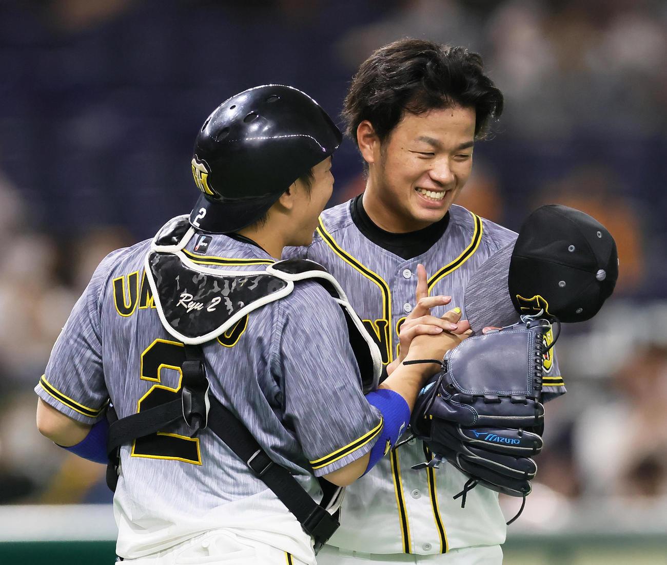 巨人対阪神 プロ初完封勝利を飾った阪神高橋(右)は梅野と笑顔でタッチを交わす(撮影・足立雅史)