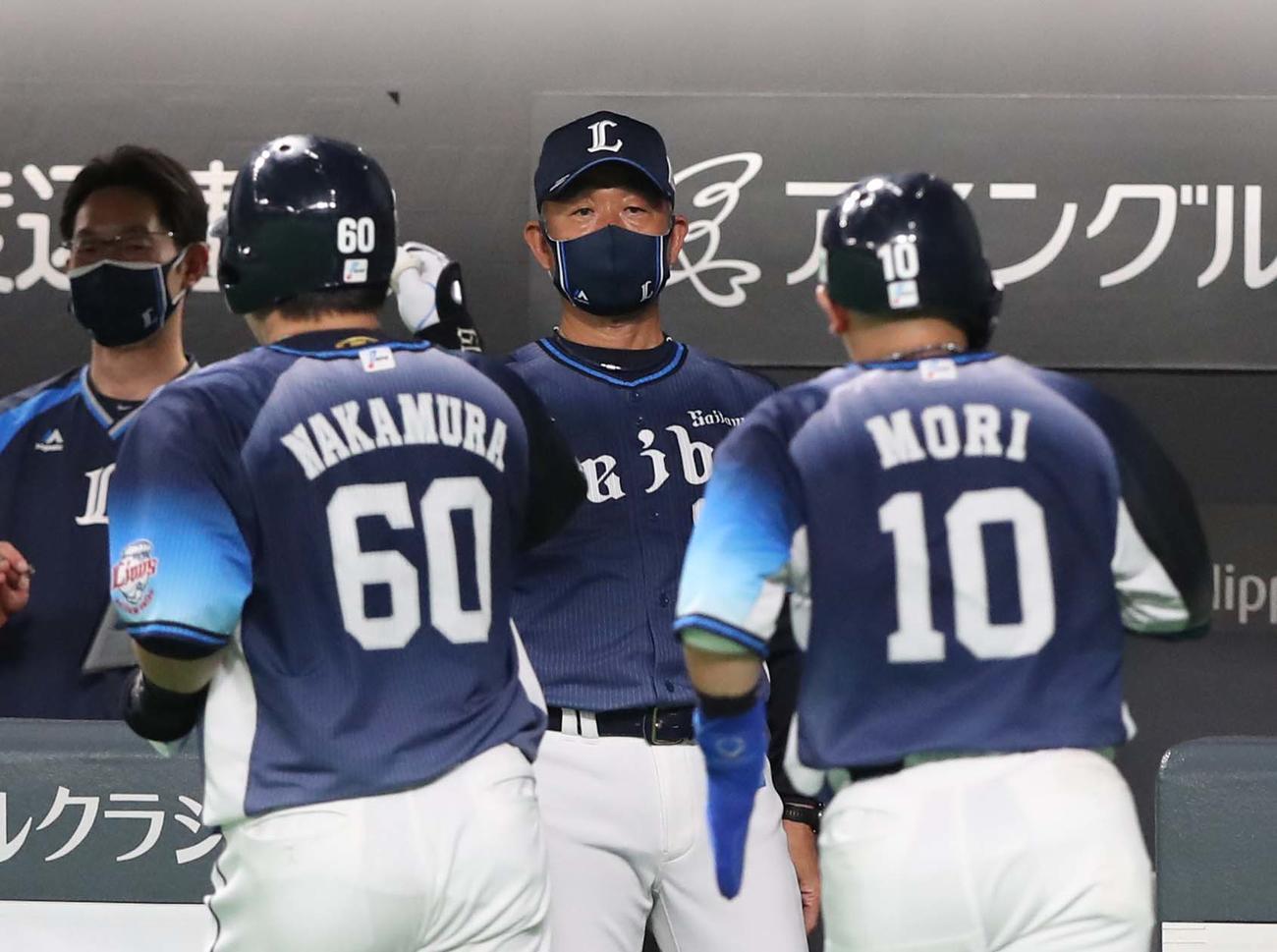 14日の日本ハム戦の6回表、2点本塁打を放った中村(左)を出迎える辻監督(撮影・黒川智章)