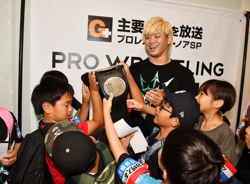 清宮海斗(中央)のチャンピオンベルトに触る日刊スポーツのジュニア記者たち(撮影・柴田隆二)