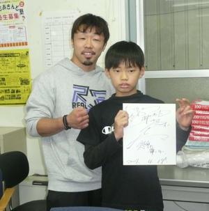 ボクシングジムに通う小学6年の佐藤仁くん(右)にサイン色紙をプレゼントする元世界3階級制覇王者・八重樫
