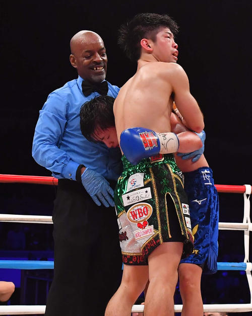 12Rを戦い抜き、死力を尽くして倒れそうな田口良一を支えるWBO世界フライ級王者・田中恒成(撮影・上田博志)