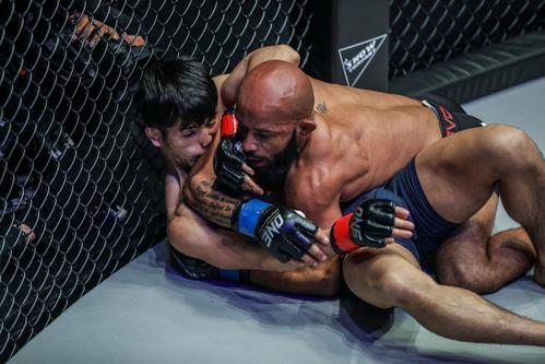 ケージ際で寝技の攻防を展開する元UFCフライ級王者デミトリアス・ジョンソン(右)と若松佑弥