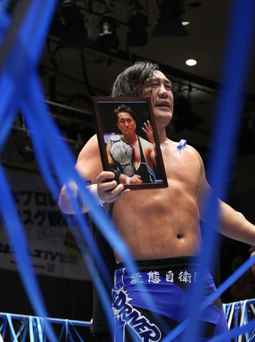 故青木篤志の写真を手に、観客にあいさつをする佐藤(撮影・河田真司)