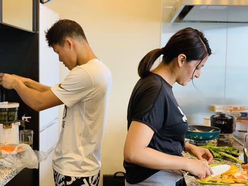 自宅キッチンで食事を作る亀田和毅(左)と妻シルセさん(シルセさん提供)