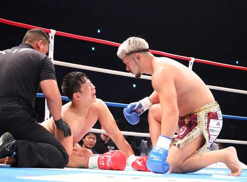 第1R、KOで敗れ険しい表情のヤン・ジェグン(左)の元に寄り、言葉を交わす愛鷹(撮影・河田真司)