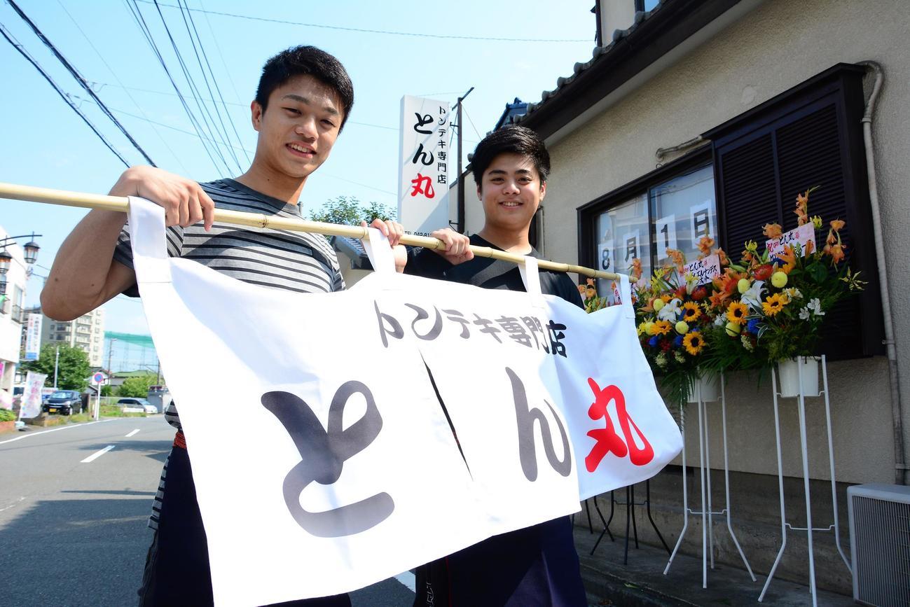 「トンテキ専門店とん丸」ののれんを手にする中谷潤人(中央)と弟龍人さん