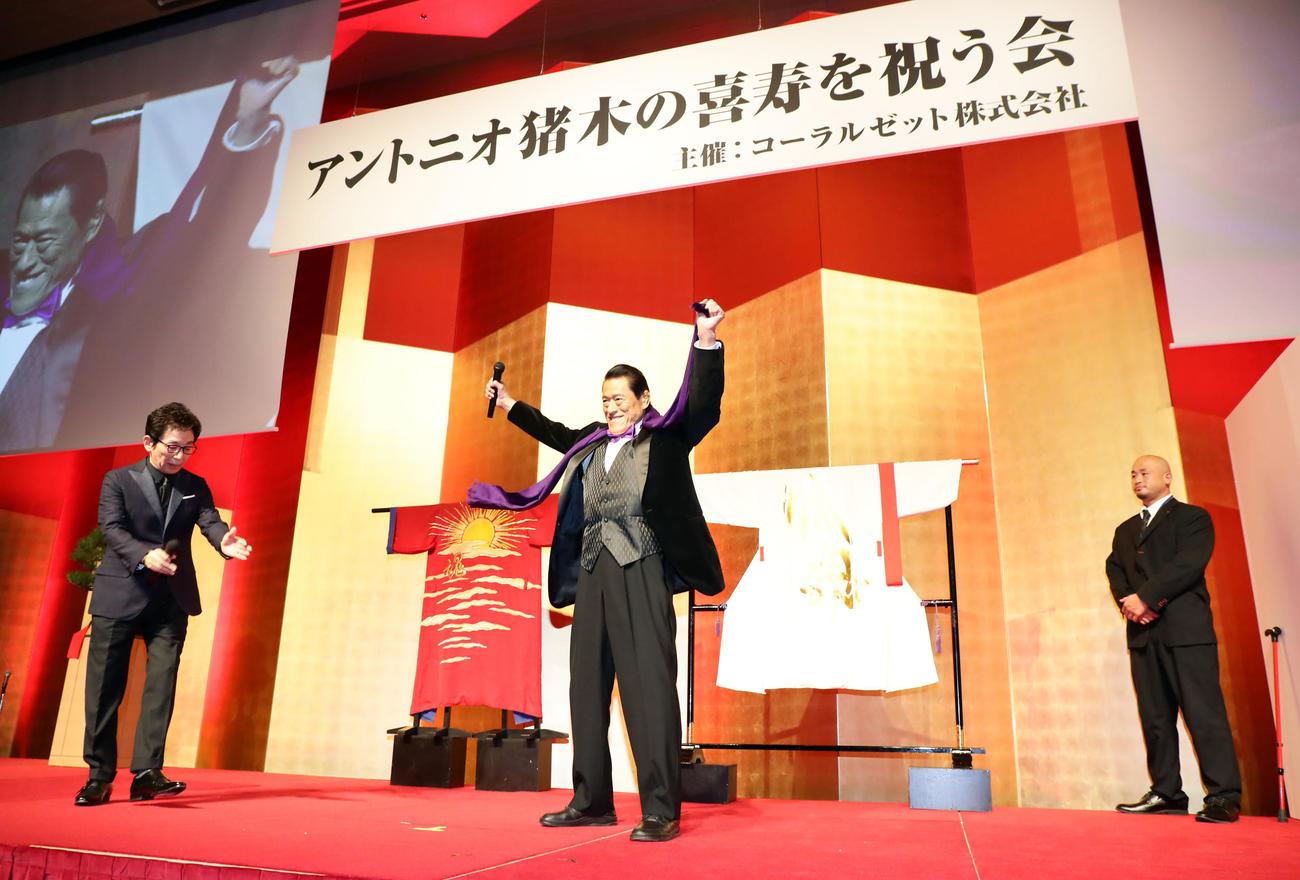 「アントニオ猪木の喜寿を祝う会」で、古舘伊知郎アナウンサー(左)の呼び込みで登場したアントニオ猪木氏(中央)(撮影・浅見桂子)