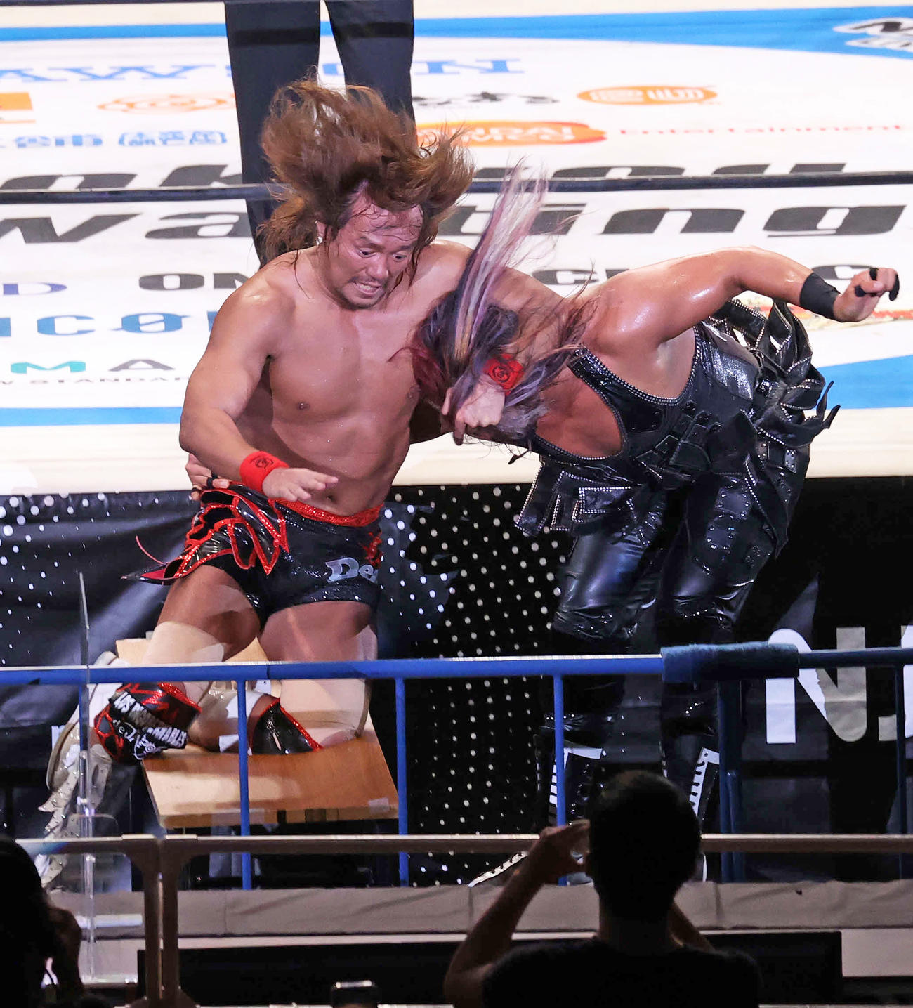 内藤哲也(左)の膝を机にぶつけるEVIL(撮影・鈴木正人)