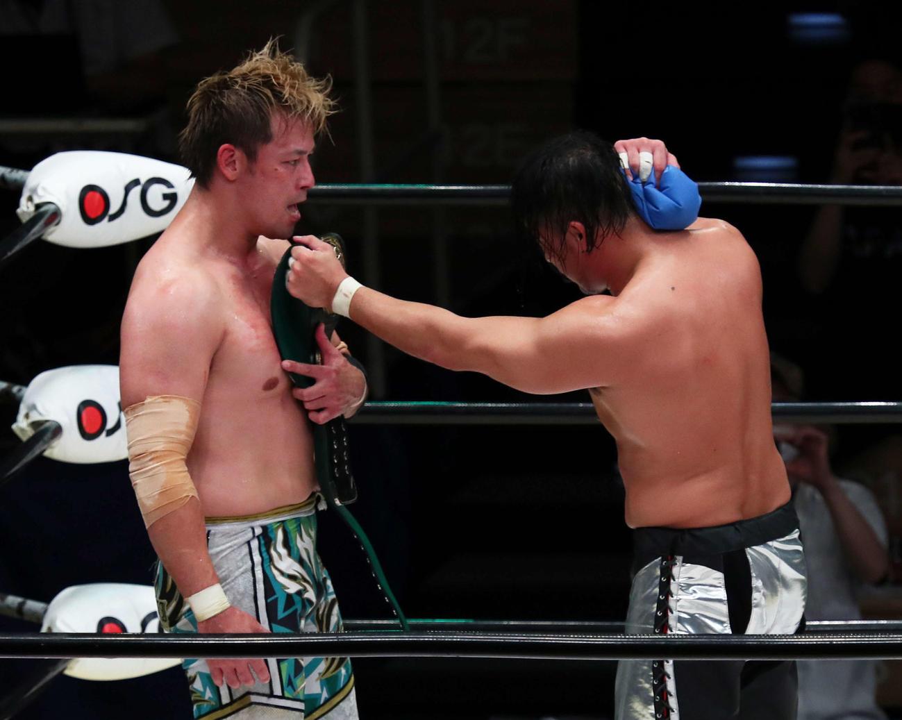 防衛に成功した潮崎(左)は丸藤からベルトを受け取る(撮影・足立雅史)