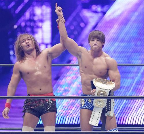 内藤哲也(左)から奪った2本のIWGPチャンピオンベルトを手に指を突き上げる飯伏幸太(撮影・菅敏)