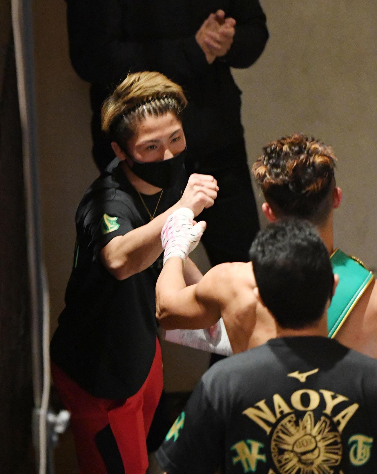 試合に勝利した弟・拓真(右)とタッチをかわす井上尚(撮影・横山健太)