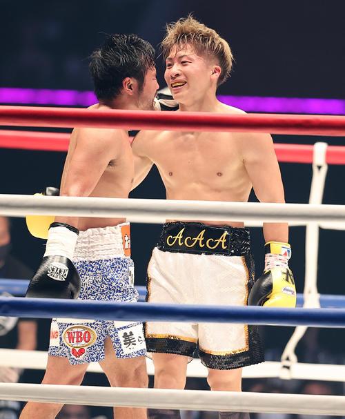 3回、ヘッドギアを取っての打ち合いを終え、笑顔で健闘を称え合う井上(右)と比嘉(撮影・浅見桂子)