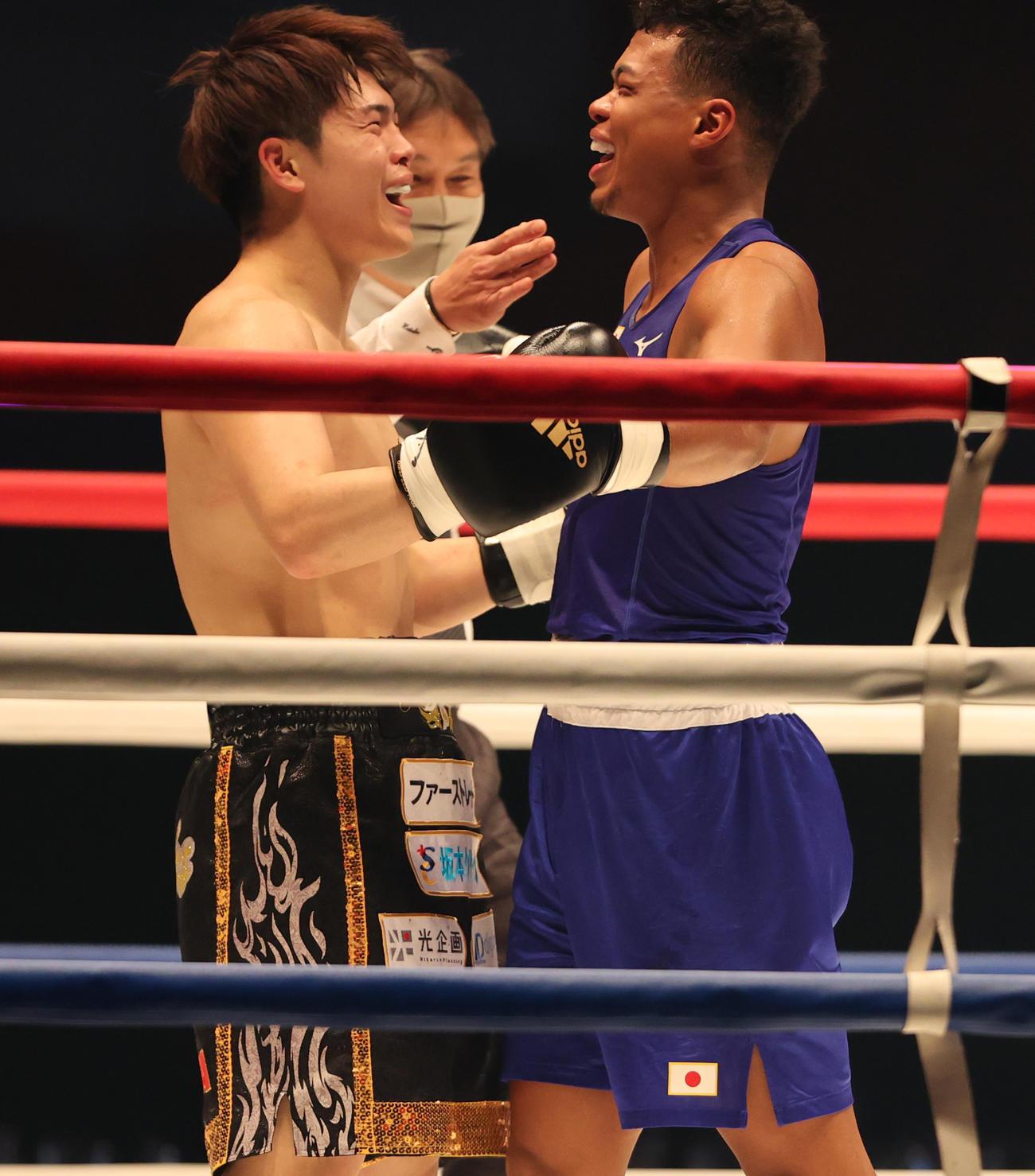 戦いを終え抱きあう佐々木(左)と岡沢(撮影・野上伸悟)