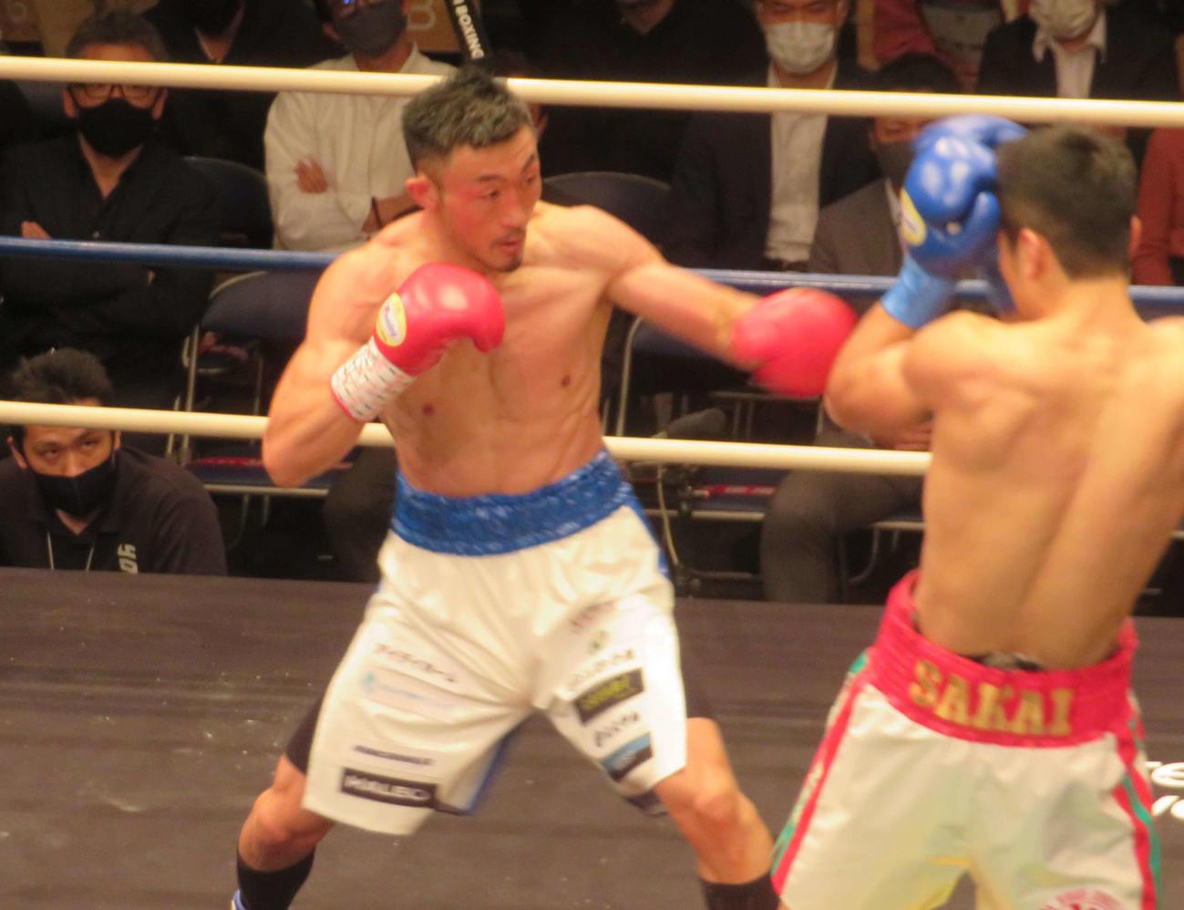 挑戦者の坂井(右)を攻め込む日本ウエルター級王者小原