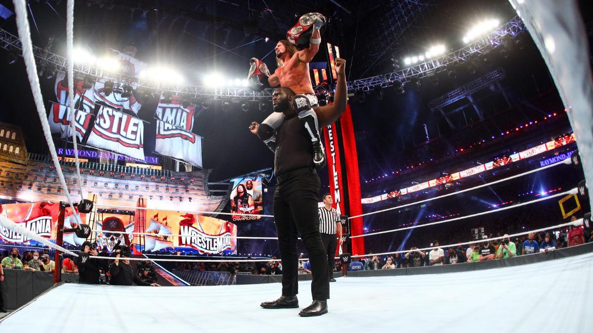 オモス(下)に肩車されながらロウタッグ王座ベルトを誇示するAJスタイルズ(C)2021 WWE, Inc. All Rights Reserved.
