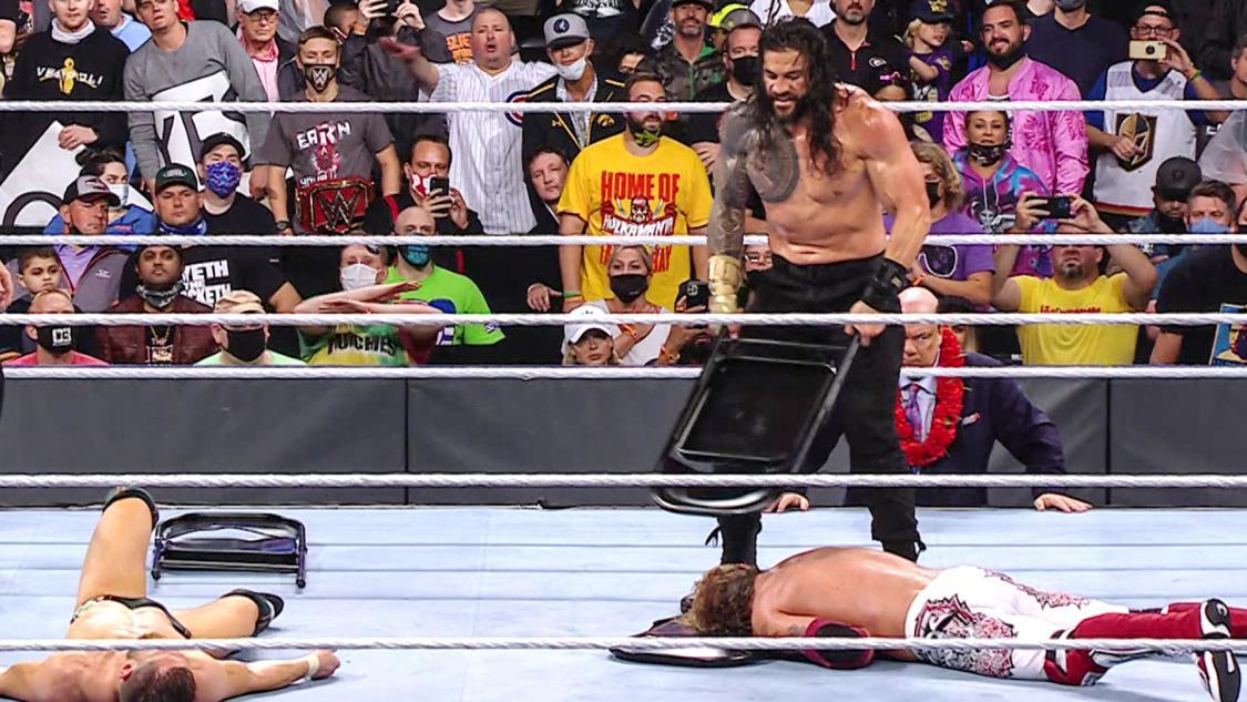 ブライアン(手前左)、エッジ(手前右)にパイプいす攻撃を加えるWWEユニバーサル王者レインズ(C)2021 WWE, Inc. All Rights Reserved.