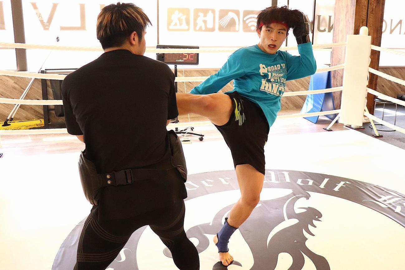 同門の先輩、小沢(左)の持つミットに強烈な右ミドルキックを放った松本(C)K-1
