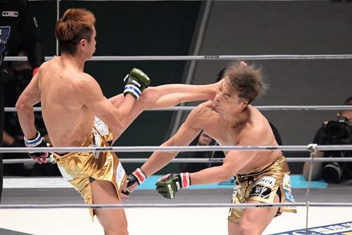 1回、試合開始直後に久保(左)のカウンターの蹴り浴びる太田(撮影・滝沢徹郎)