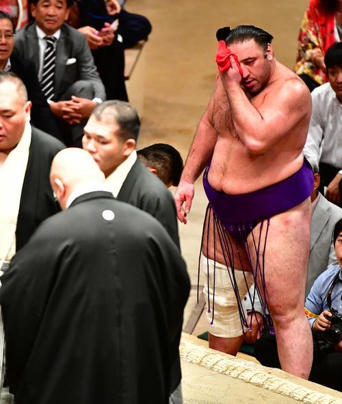 流血した顔面をタオルで押さえながら審判団の協議を待つ栃ノ心(撮影・小沢裕)