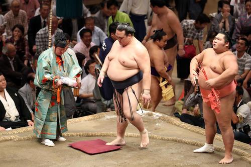 千代大龍(右)に押し出しで敗れ、座布団を踏みながら悔しがる稀勢の里(撮影・狩俣裕三)