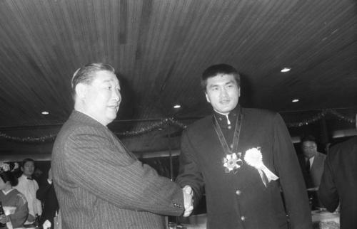 学生横綱祝勝会の席で花籠部屋入りを表明した輪島さんは、花籠親方(左)と握手(1969年12月16日撮影)