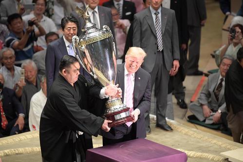 大相撲夏場所千秋楽 表彰式で「アメリカ合衆国大統領杯」を持ち上げて笑顔を見せるドナルド・トランプ大統領(右)。後方は拍手を送る安倍晋三首相(撮影・加藤諒)