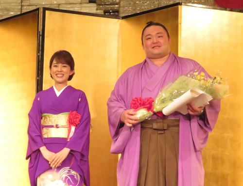 富山県人会で、同じ特別ゲストの演歌歌手丘みどり(左)から花束を受け取り、笑顔を見せる朝乃山