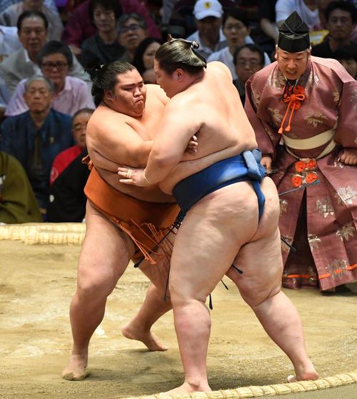 御嶽海(左)は逸ノ城を押し出しで破る(撮影・前岡正明)