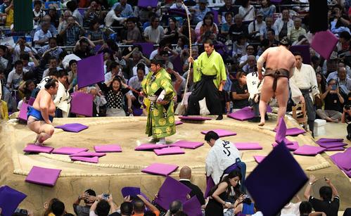 大相撲名古屋場所14日目 琴奨菊(右)が寄り切りで白鵬に勝利、客席から座布団が投げられる(撮影・奥田泰也)