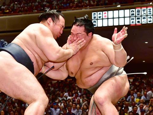 立ち合いで北勝富士(右)の顔面を両手で突く鶴竜(撮影・小沢裕)