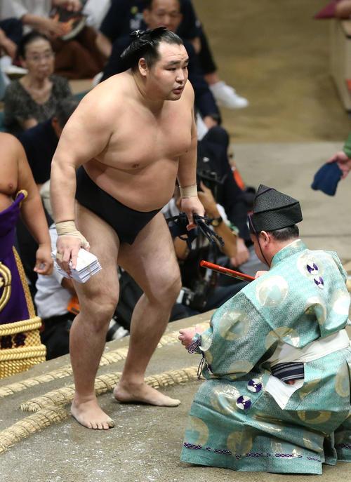 碧山を下し、懸賞金の束を手に土俵から引き揚げる鶴竜(撮影・河田真司)