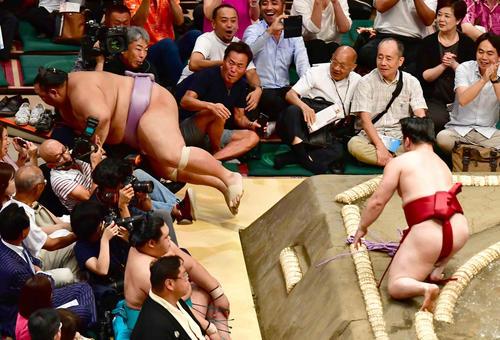 炎鵬(右)に寄り切りで敗れた琴勇輝は土俵に落ちた勢いでカメラマンに突っ込む(撮影・小沢裕)