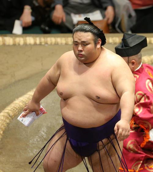 懸賞金の束を手に土俵から引き揚げる貴景勝(撮影・河田真司)